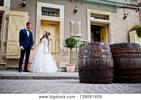 Wedding Couple Near Vintage Building With Two Barrel