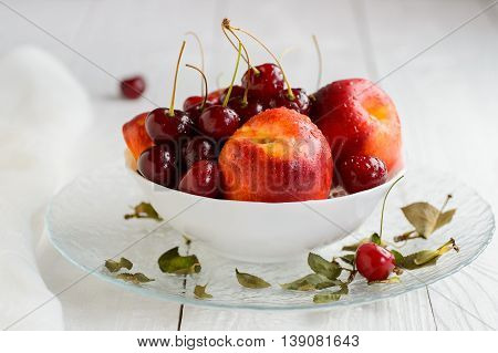 Nectarines cherries with water droplets in white bowl on wooden table