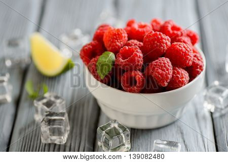 fresh raspberries in a white bowl on a wooden table
