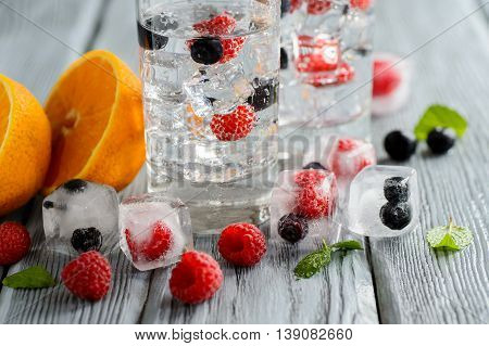Cold cocktail with forest berries frozen in ice cubes on wooden table