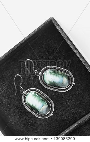 Green agate earrings in black jewel box as a background