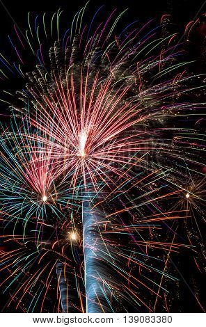 Multiple fireworks with various colors exploding overhead.
