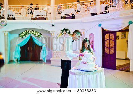 Newlywed cut wedding cake at restaurant at wedding