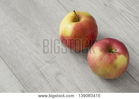 Pair of red apples on gray wooden background
