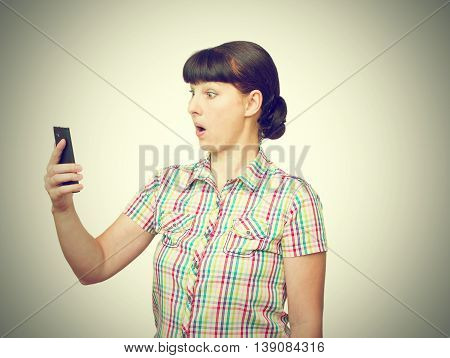 The Young Woman Stares At The Phone Screen.