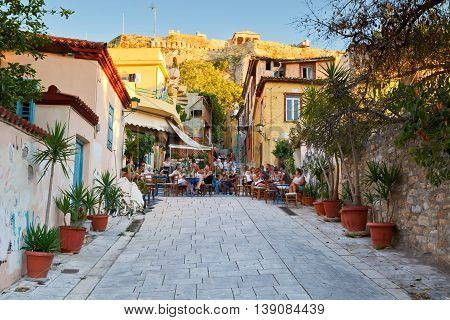 ATHENS, GREECE - JULY 17, 2015: People in coffee shops in the old town of Plaka under Acropolis, Athens on July 17, 2015.