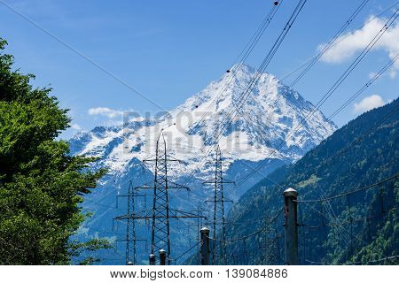 Electric poles in front of Alps mountain covered by snow in Switzerland