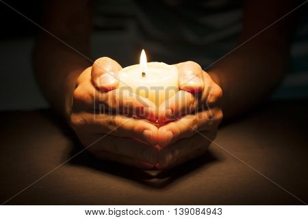 Praying Hands with candle in black background
