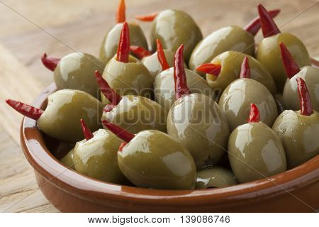 Pickled olives stuffed with red pepper in a bowl