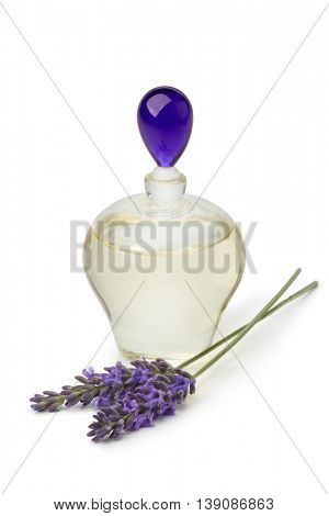 Bottle with lavender oil and purple flowers on white background