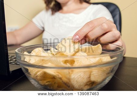 Close-up of a hand of a young women taking potato crisps