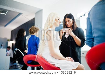 Young Beautiful Blonde Bride Applying Wedding Make Up By Makeup Artist
