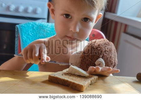 The boy holds a knife and smears cheese on toast toasted bread with a slice of cheese sitting at a table in the kitchen.