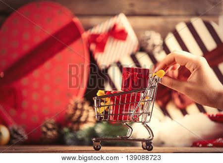 Female Hand Holding Cart With Gifts