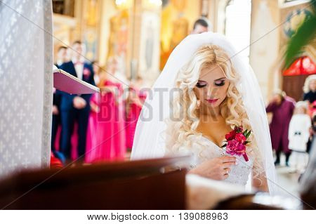 Style blonde bride kneeling at church at wedding