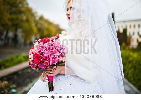 Portrait Of Charming Blonde Bride In A Fur Coat With Bouquet