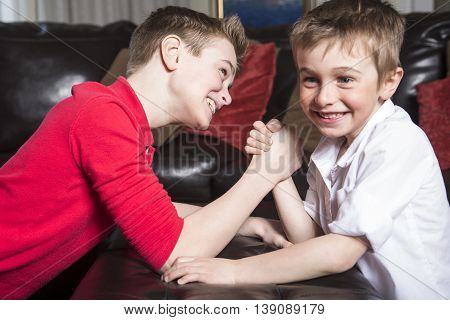 two brothers compete in arm wrestling  at home