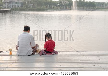 Bangkok, Thailand - March 2016: father and girl sit together feeding fish at pier in home village park pond lovely family activity on holiday, weekend.