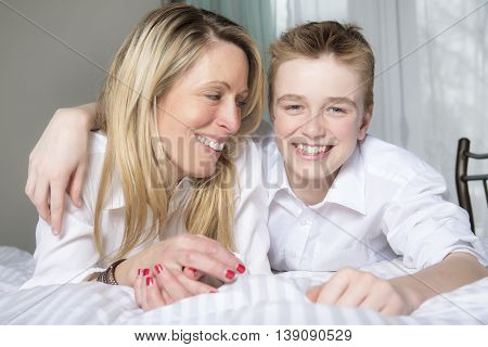 A Mother And Son Relaxing Together In Bed