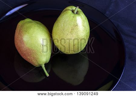 Fragrant pears . sweet fragrant flavor and aroma on black dish