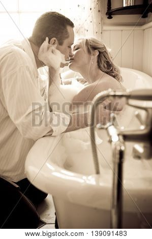 Couple playful bubble bath kiss while on holiday.