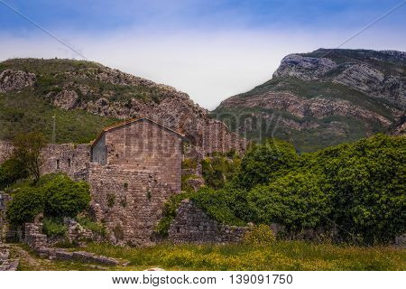 A cloudy evening in the mountains. The completion of the archaeological expedition. Ruins of the ancient city in the mountains in the evening. Foggy view of old stone buildings and streets.