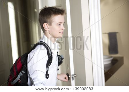 a teen coming home passing through the door.