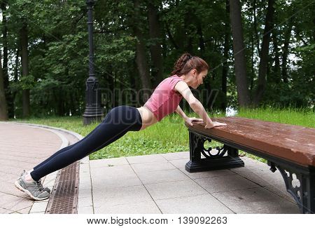 Young girl doing push-ups on bench outdoors in the afternoon. In the park.