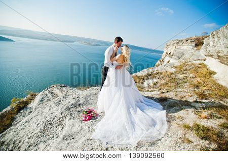 Charming Bride And Elegant Groom On Landscapes Of Mountains, Water And Blue Sky At Sunny Weather