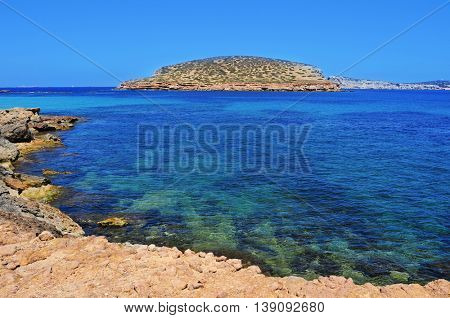 a view of the Southern coast of Sant Antoni de Portmany, in Ibiza Island, Spain, with the Illa des Bosc island in the background