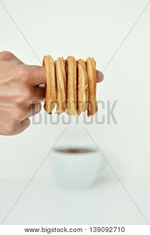 closeup of the hand of a young man with some Spanish churros in his forefinger and a cup of hot chocolate in the background