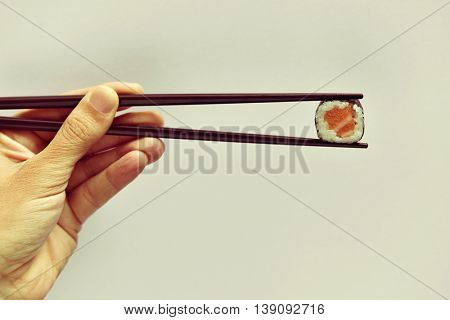 closeup of a young man picking a salmon makizushi with a pair of chopsticks, against an off-white background