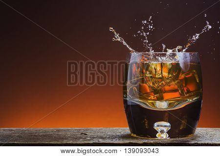 Rustic Glass of Whisky on wood with splash
