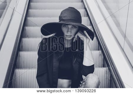 Gorgeous young brunette with hat posing on an escalator