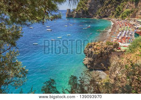 Summertime sescape: Amalfi Coast (Costiera Amalfitana).The best beaches in Italy:Positano seaside (Campania).Beach set in the cliff: the background a watchtower.