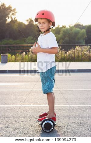 Boy Stands On The Black Gyro Scooter Outdoors