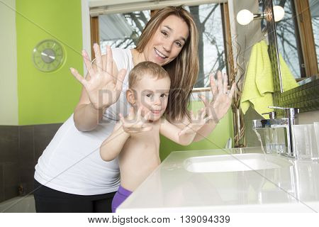 A Happy mother and kid wash hands with soap in bathroom
