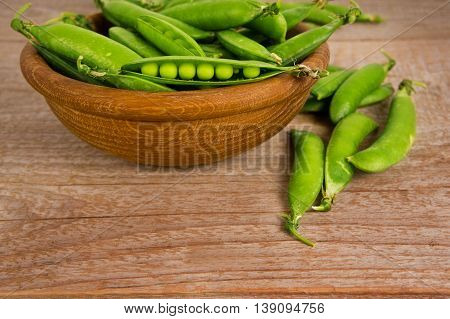 Green peas in wooden bowl on wooden background.