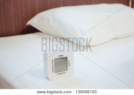 White Alarm clock on white bed sheet and White pillow in bed Room. Waking Up in a Hotel Photo Concept.