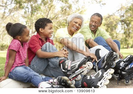 Grandparent With Grandchildren Putting On In Line Skates In Park