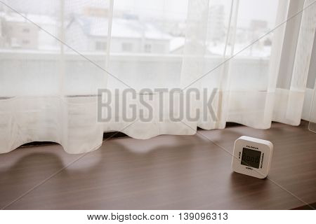 White Alarm Clock On Wood Bar Near The Window