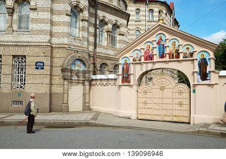 17.07.2016.Russia.Saint-Petersburg.A man looks on the faces of the saints on the gates of the temple.