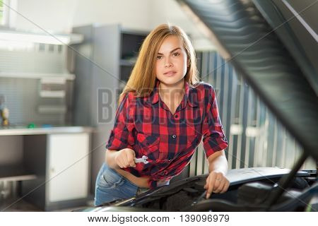 Young sexy brunette mechanic in checked shirt in garage. Auto diagnostic