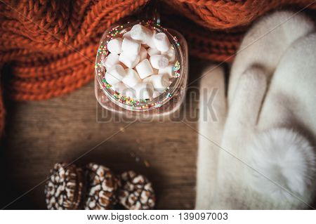 Warm cocoa with marshmallows chocolate chip cookies knitted orange scarf and white mittens on wooden background
