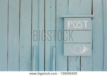 Blue post box on a wooden blue wall