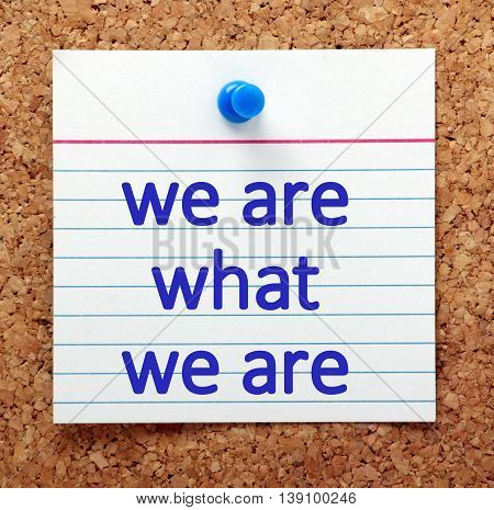 The words We Are What We Are on a note card pinned to a cork notice board as a reminder that we should think positively about and accept who we are