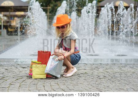 Elegant Charming cute little girl in fashionable clothes sunglasses orange hat sitting with full shopping bags. Reviewing purchases. Shopping bags on pavement. Fountain in background.