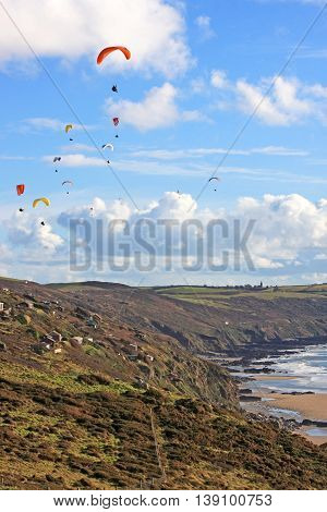 Paragliders flying above the coast at Freathy, Cornwall