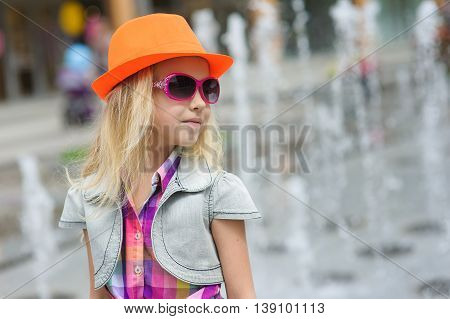 Portrait of girl in fashionable clothes. Elegant Charming cute little girl in sunglasses orange hat. Fountain in background. Looking to side.