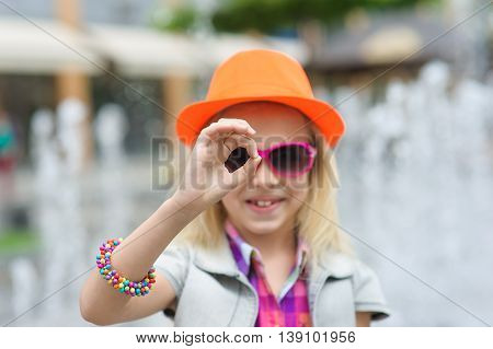 Portrait of girl in fashionable clothes. Elegant Charming cute little girl in sunglasses orange hat. Fountain in background. Girl making hand gesture ok.